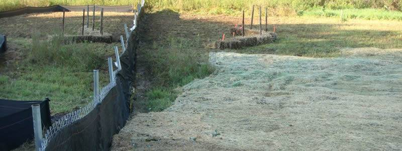 Silt fence with chain link wire mesh is set on the grassland.