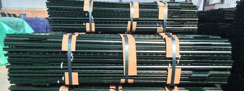 There are pallets of T-posts with green coated piled up in the yard.