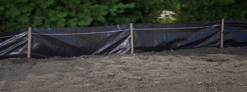 Silt fence fabrics are assembled with wood stakes and set on the soil.