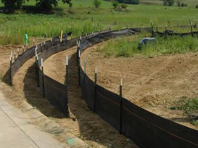 Silt fences with metal posts are set on the slope.