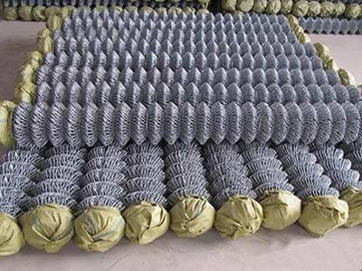 Both edges of chain link wire meshes for silt fencing are covered with yellow woven bags.